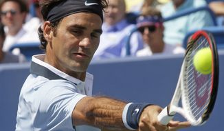 Roger Federer, from Switzerland, hits a backhand against Tommy Haas, from Germany, during a match at the Western & Southern Open tennis tournament, Thursday, Aug. 15, 2013, in Mason, Ohio. (AP Photo/Al Behrman)