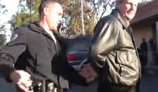 """Mark Mackey is arrested outside a California DMV in 2011 for reading a bible out loud to """"a captive audience."""" All charges have been dropped against him. (Image: YouTube)"""