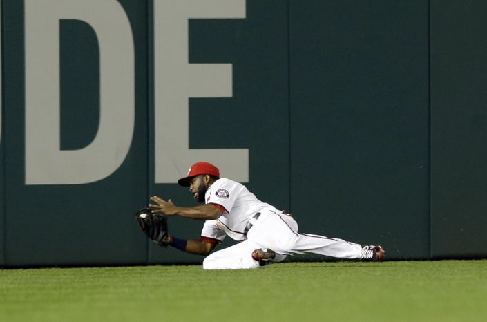 Washington Nationals center fielder Denard Span hangs onto a game-winning catch in the ninth inning of the Nationals' 6-5 victory over the San Francisco Giants. (Associated Press photo)