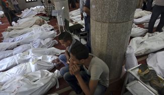 Egyptians mourn over the bodies of their relatives in El-Iman mosque at Nasr City, Cairo, Egypt, Thursday, Aug. 15, 2013. (AP Photo/Khalil Hamra)