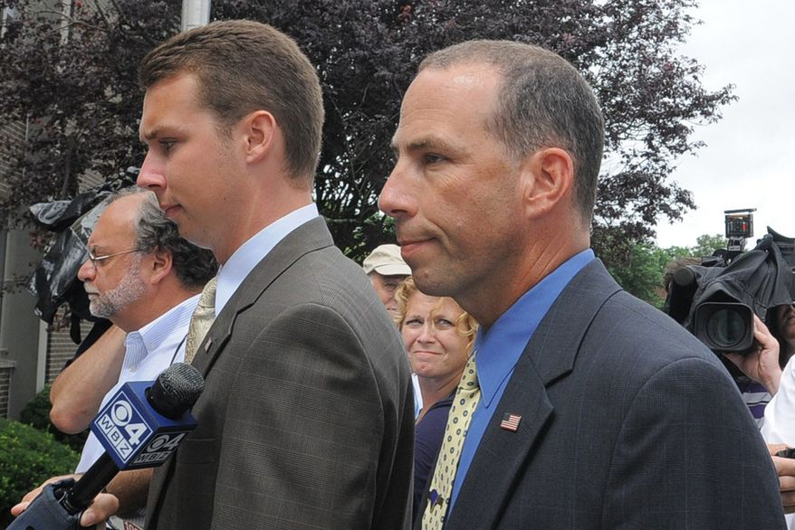 ** FILE ** Massachusetts State Police Sgt. Sean Murphy, right, a tactical photographer, and his son Connor Patrick Murphy, arrive at State Police Headquarters for his hearing to determine his duty status after he released images of the arrest of the Boston Marathon bombing suspect, in Framingham, Mass., Tuesday, July 23, 2013. (AP Photo/The Boston Herald, Ted Fitzgerald)