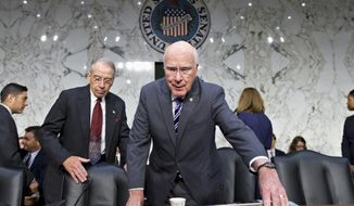 **FILE** Senate Judiciary Committee Chairman Patrick Leahy (right), Vermont Democrat, and the committee's ranking Republican, Chuck Grassley of Iowa, arrive on Capitol Hill on July 31, 2013, as the panel questioned top Obama administration officials about the National Security Agency's surveillance programs for the first time since the House narrowly rejected a proposal last week to effectively shut down the NSA's secret collection of hundreds of millions of Americans' phone records. (Associated Press)