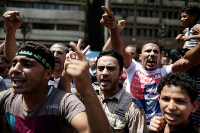 Supporters of Egypt's ousted President Mohammed Morsi chant slogans against Egyptian Defense Minister Gen. Abdel-Fattah el-Sissi before clashes broke out with Egyptian security forces in Ramses Square, downtown Cairo, Egypt, Friday, Aug. 16, 2013. (AP Photo/Hassan Ammar)