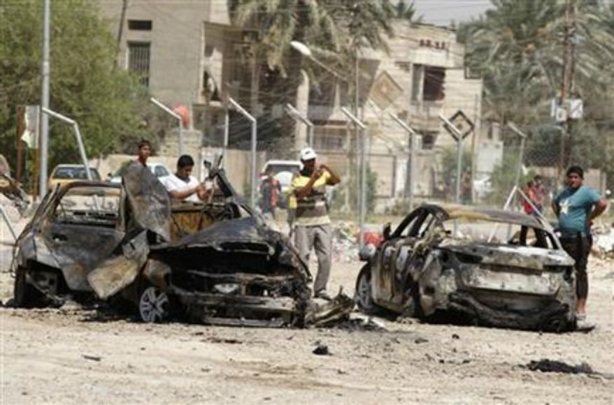 Civilians inspect the aftermath of a car bomb attack in Baghdad, Iraq, Thursday, Aug. 15, 2013. A wave of car bombs in the Iraqi capital on Wednesday killed 26 people and wounded dozens, the latest attacks in a months-long surge in violence. (Associated Press)