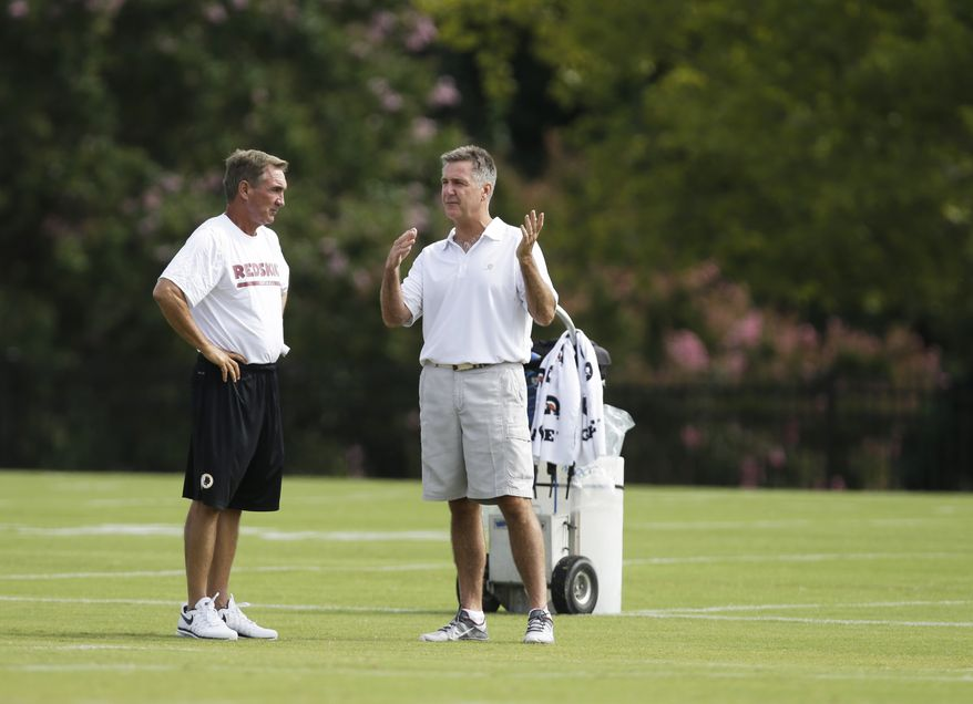 Washington Redskins head coach Mike Shanahan, left, talks with general manager Bruce Allen during the NFL football teams training camp practice in Richmond, Va. Monday, July 29, 2013. (AP Photo/Steve Helber)