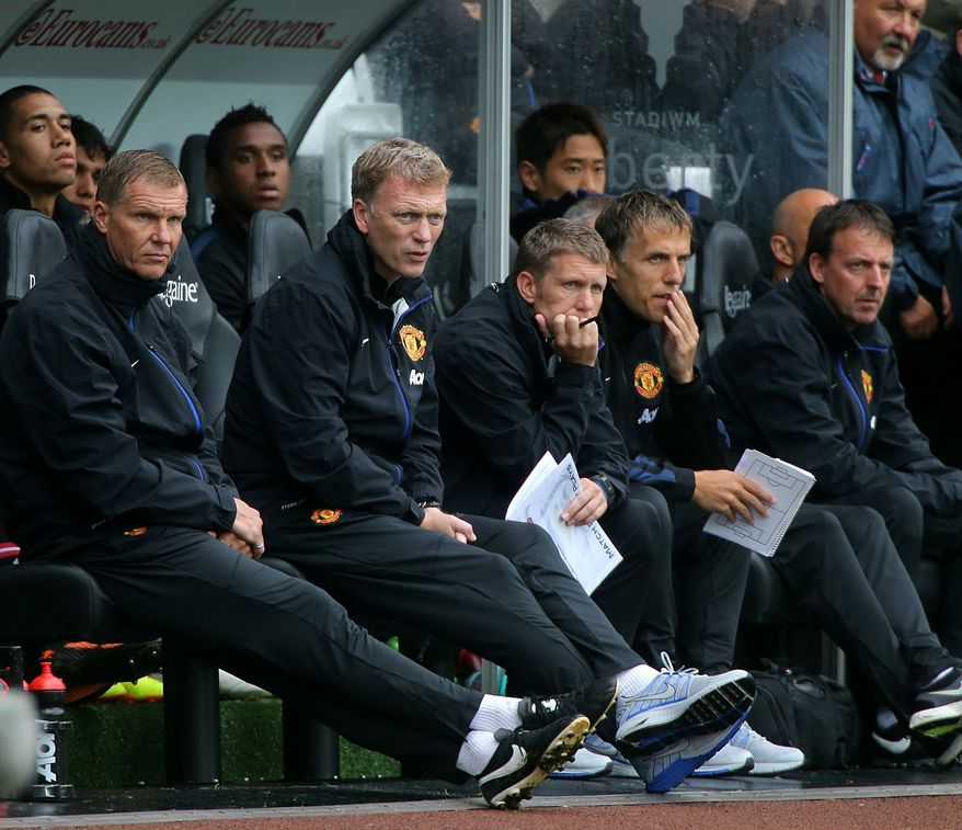 Manchester United manager David Moyes, front second left, watches his team from the dugout during their English Premier League soccer match against Swansea City at the Liberty Stadium, Swansea, England, Saturday Aug. 17, 2013. (AP Photo / Nick Potts, PA)