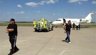Dave Ungar, the tour manager for the rock band Dokken, left, and Craig Bradford, tour manager for Ratt, walk away from a charter jet that had to make an emergency landing, Saturday, Aug. 17, 2013, in Moline, Ill. (AP Photo/Courtesy Chuck Brennan)