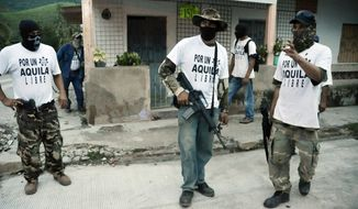 "**FILE** This photo shows armed members of a local self-defense group wearing white T-shirts with the slogan ""For a Free Aquila"" stand at a street corner in the town of Aquila, Mexico, on  July 23, 2013. At least 23 bodies were found in two neighboring states in western Mexico where drug cartels, vigilantes and security forces have been fighting for much of the year, authorities said on Aug. 17, 2013. The state prosecutor in Michoacan said that nine bodies, hands bound and shot, were found on an abandoned property near the town of Buenavista Tomatlan along with a sign indicating they may have been members of the Knights Templar cartel. (Associated Press)"