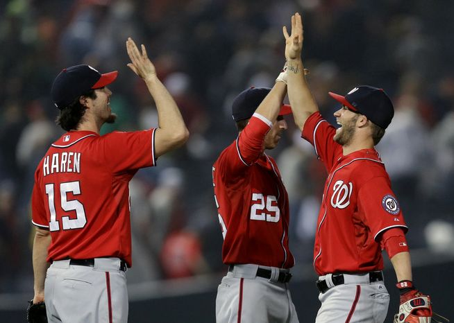 The Washington Nationals celebrate after defeating the Braves in an epic 15-inning affair that lasted five hours and 29 minutes. (Associated Press Photo)