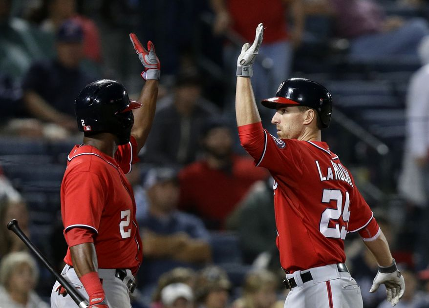 Washington Nationals center fielder Denard Span, left, congratulates first baseman Adam LaRoche, right, on his game-winning home run in the 15th inning on Saturday night against the Atlanta Braves. (Associated Press photo)