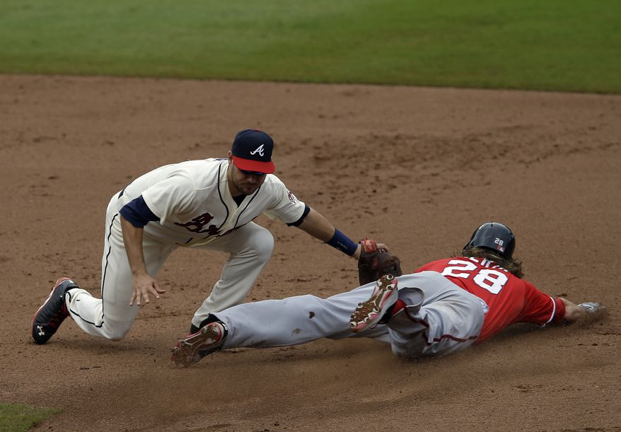 Atlanta Braves third baseman Paul Janish (4)prepares to tag out Washington Nationals right fielder Jayson Werth (28) on a steal attempt in the sixth inning of a a baseball game in Atlanta, Sunday, Aug. 18, 2013. (AP Photo/John Bazemore)