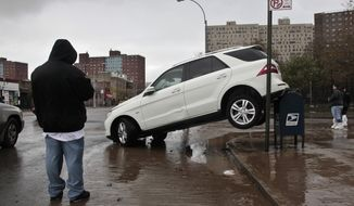 **FILE** The tail end of a SUV is perched on top of a postal mailbox in the aftermath of floods from Hurricane Sandy in Coney Island, N.Y., on Oct. 30, 2012. (Associated Press)