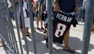 Fans line up behind a barrier to exchange their New England Patriots Aaron Hernandez football jerseys at Gillette Stadium in Foxborough, Mass., Saturday, July 6, 2013. The Patriots are offering a new jersey to all fans who want to get rid of the one they bought with Hernandez's name on it. (AP Photo/Michael Dwyer)