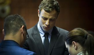 South African runner Oscar Pistorius (center) cries as he prays with his sister Aimee and brother Carl in the magistrates court in Pretoria, South Africa, on Monday, Aug. 19, 2013. Mr. Pistorius was indicted Monday on charges of murder and illegal possession of ammunition in the shooting death of his girlfriend, Reeva Steenkamp. (AP Photo)