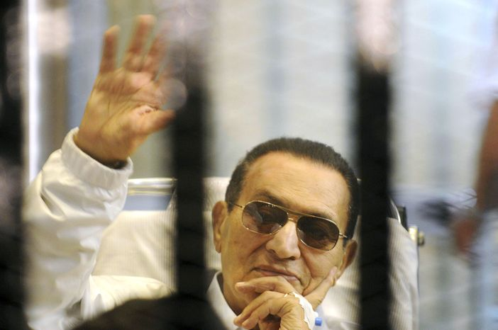 ** FILE ** Former Egyptian President Hosni Mubarak waves to his supporters from behind bars as he attends a hearing in his retrial on appeal in Cairo on Saturday, April 13, 2013. (Associated Press)