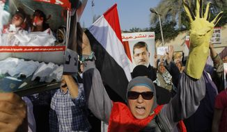 "A supporter of Egypt's ousted President Mohammed Morsi shouts slogans as she holds a poster showing victims of recent clashes with security forces during a march in Maadi, Egypt, on Aug. 19, 2013. Arabic on Morsi poster reads, ""Yes to legitimacy."" (Associated Press)"