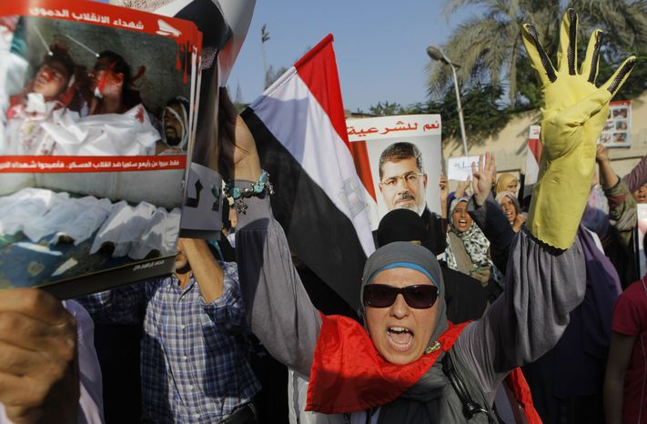 """A supporter of Egypt's ousted President Mohammed Morsi shouts slogans as she holds a poster showing victims of recent clashes with security forces during a march in Maadi, Egypt, on Aug. 19, 2013. Arabic on Morsi poster reads, """"Yes to legitimacy."""" (Associated Press)"""