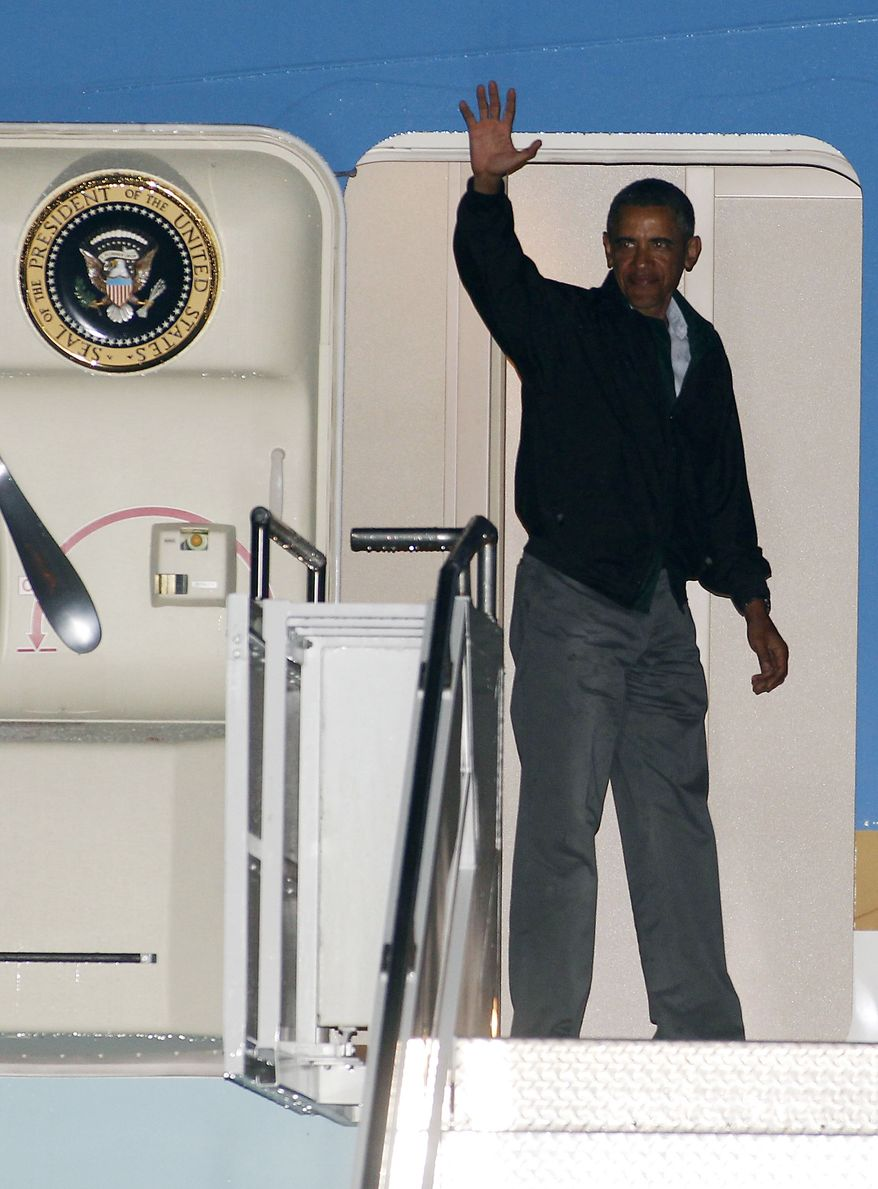 President Obama waves from the door of Air Force One at the Cape Cod Coast Guard Station in Bourne, Mass.,  on Sunday, Aug. 18, 2013, after ending his vacation on Martha's Vineyard. (AP Photo/Stew Milne)