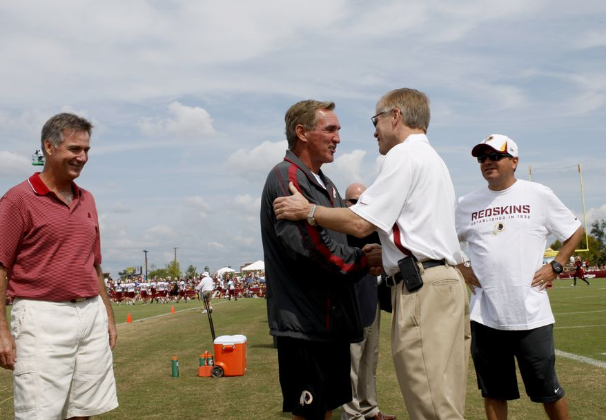 Washington Redskins head coach Mike Shanahan, center left, greets Virginia Gov. Bob McDonnell, center right, with general manager Bruce Allen, left, and owner Dan Snyder, right, looking on at the football team training camp in Richmond, Va., Friday, Aug. 16, 2013. (AP Photo/Richmond Times-Dispatch, Daniel Sangjib Min)