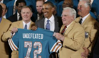 Former Miami Dolphins football quarterback Bob Griese (left), Hall of Fame Dolphins Coach Don Shula (second from right) and Larry Csonka (right) pose for photographs with President Obama and a signed team jersey during a ceremony at the White House on Aug. 20, 2013, where the president honored the Super Bowl VII Champion Dolphins. The '72 Dolphins remain the only undefeated team in NFL history. (Associated Press)