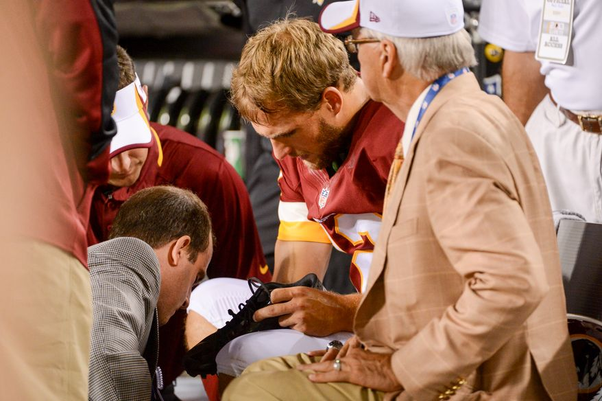 Washington Redskins quarterback Kirk Cousins (12) is looked at by team staff on the sideline after leaving the game with a foot injury in the second quarter as the Washington Redskins play the Pittsburgh Steelers in NFL preseason football at FedEx Field, Landover, Md., Monday, August 19, 2013. (Andrew Harnik/The Washington Times)
