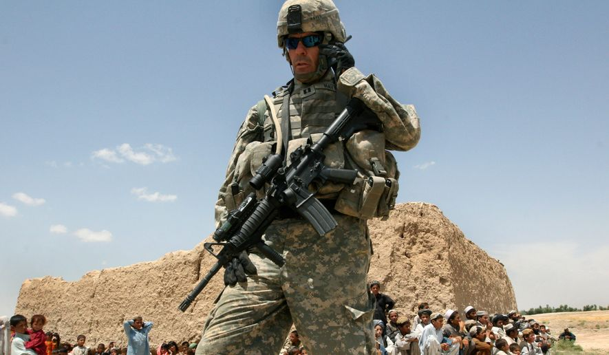 A U.S. soldier talks on the phone as Afghan children wait to receive Afghan National Army's humanitarian aid in the Andar district of Ghazni province, west of Kabul, Afghanistan on June 22, 2007. (Associated Press) ** FILE **