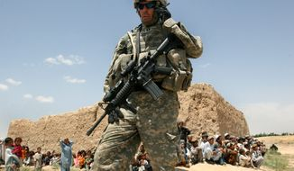 **FILE** A U.S. soldier talks on the phone as Afghan children wait to receive Afghan National Army's humanitarian aid in the Andar district of Ghazni province, west of Kabul, Afghanistan on June 22, 2007. (Associated Press)