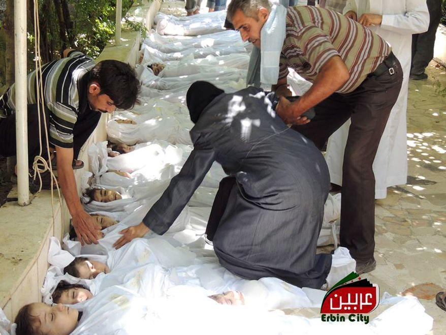 """This citizen journalism image provided by the Local Committee of Arbeen, authenticated based on its contents and other AP reporting, shows a Syrian man helping a woman as she mourns over the dead bodies of children after an alleged poisonous gas attack fired by regime forces, according to activists in Arbeen town in Damascus on Aug. 21, 2013. Syrian regime forces fired intense artillery and rocket barrages Wednesday on the eastern suburbs of the capital Damascus, in what two pro-opposition groups claimed was a """"poisonous gas"""" attack that killed dozens of people. (Associated Press/Local Committee of Arbeen)"""
