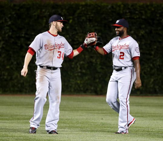 Washington Nationals left fielder Bryce Harper (34) and Denard Span (2) celebrate the Nationals' 4-2 win over the Chicago Cubs after a baseball game Tuesday, Aug. 20, 2013, in Chicago. (AP Photo/Charles Rex Arbogast)