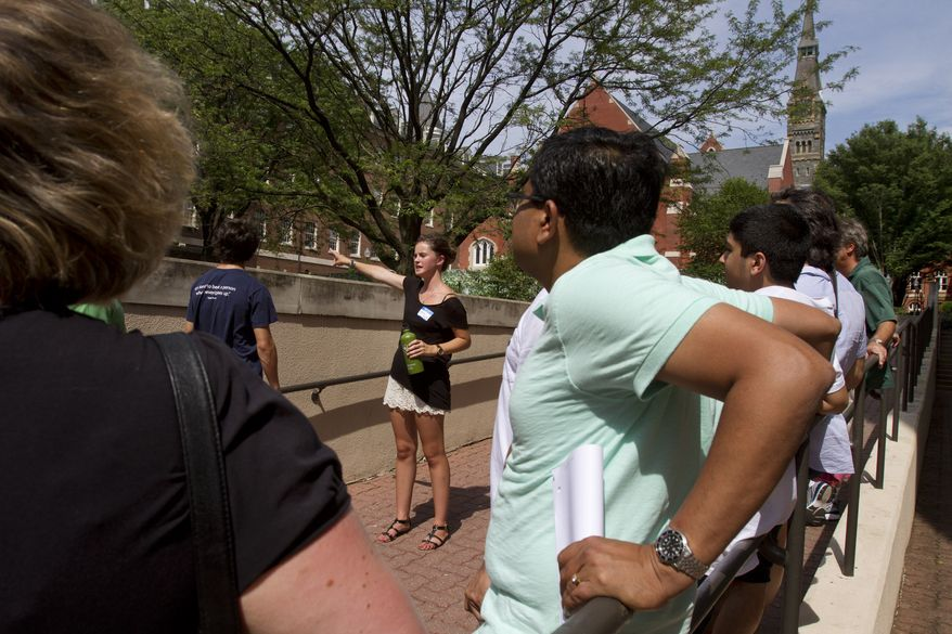 **FILE** Prospective students and their parents tour Georgetown University's campus in Washington on July 10, 2013. (Associated Press)