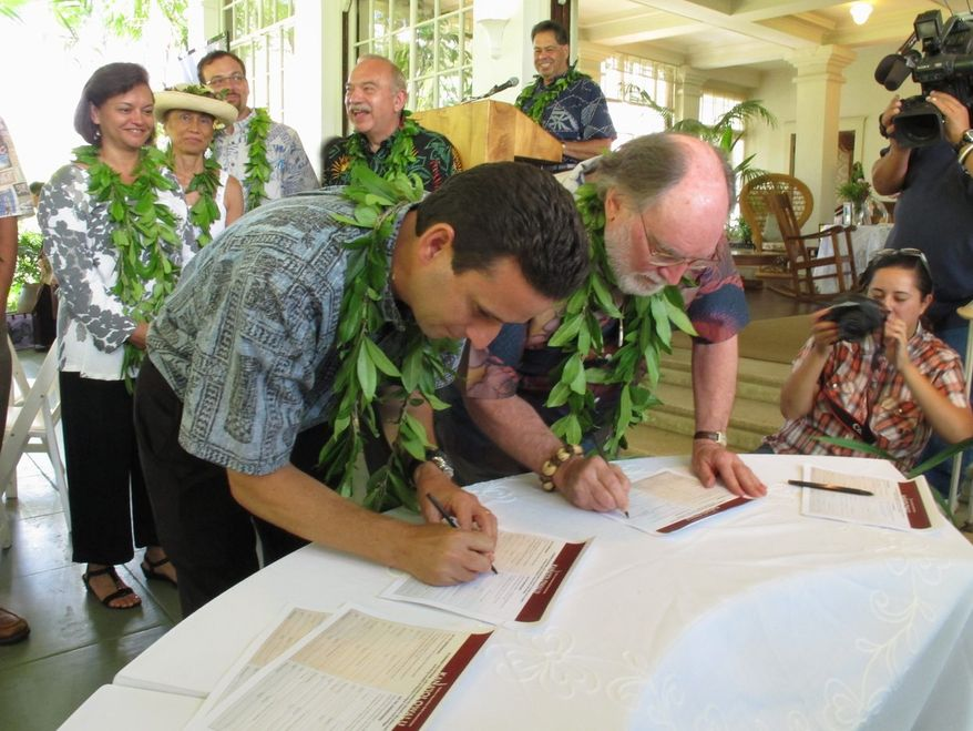 Hawaii Gov. Neil Abercrombie (right) and Lt. Gov. Brian Schatz sign a petition supporting Native Hawaiian sovereignty in Honolulu in July 2012.