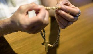 A member of the St. Thomas Korean Catholic Center prays the rosary in Anaheim, Calif. (Associated Press/File)