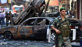 **FILE** A Lebanese army soldier passes in front of burned cars at the site of a car bomb explosion in an overwhelmingly Shiite area and stronghold of the Lebanese militant group Hezbollah, at the southern suburb of Beirut on Aug. 16, 2013. (Associated Press)