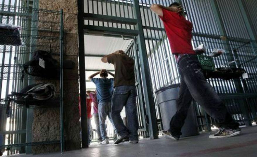 **FILE** Illegal immigrants file into a U.S. Border Patrol facility in Tucson, Ariz. (Associated Press)