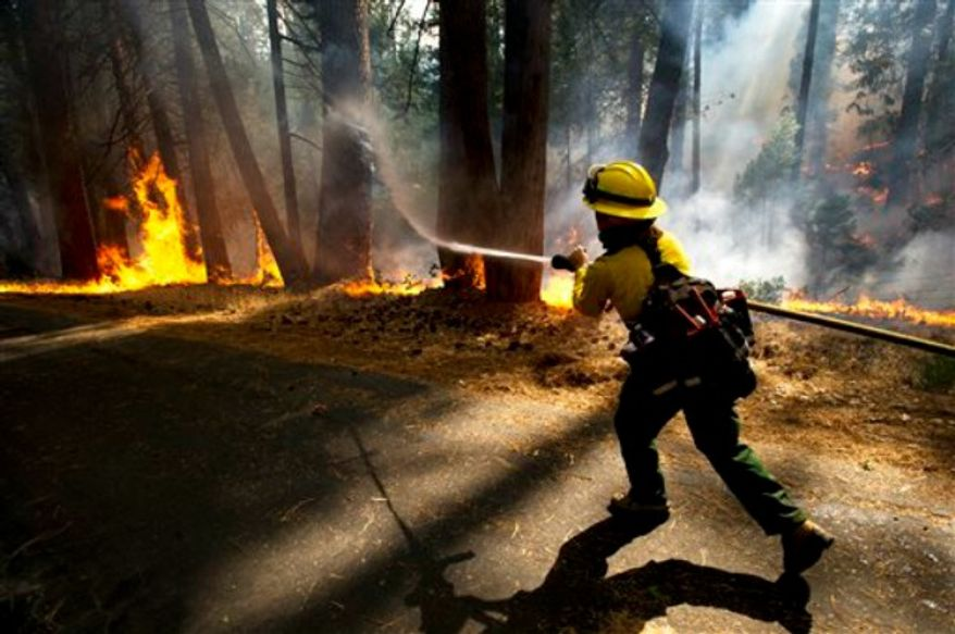 Colorado Rural Protection firefighter Molly McGee fights the Rim Fire in the Stanislaus National Forest Thursday, Aug.22, 2013. (AP Photo/The Modesto Bee, Andy Alfaro)