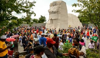 """People gather at the Martin Luther King Jr. Memorial in Washington on Saturday, Aug. 24, 2013, during a march to commemorate the 50th anniversary of the March on Washington and King's famous """"I Have a Dream"""" speech. (Andrew Harnik/The Washington Times)"""