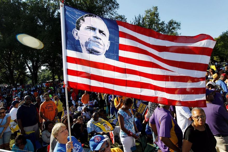Dorothy Meekins holds up the national flag with the picture of President Barack Obama as she attends the rally, commemorating the 50th anniversary of the 1963 March on Washington at the Lincoln Memorial in Washington, Saturday, Aug. 24, 2013. Organizers have planned for about 100,000 people to participate in the event, which is the precursor to the actual anniversary of the Aug. 28, 1963, march. It will be led by the Rev. Al Sharpton and King's son Martin Luther King III. (AP Photo/Jose Luis Magana)