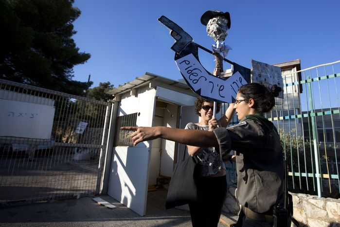 ** FILE ** An Israeli border police officer argues with an Israeli left-wing activist as she holds a protest sign during a ceremony to mark the resumption of the construction of housing units in an east Jerusalem neighborhood on Sunday, Aug. 11, 2013. (AP Photo/Sebastian Scheiner)