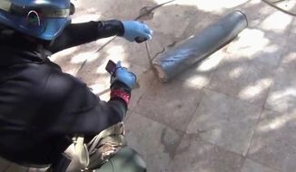 In this image taken from amateur video posted online, a presumed U.N. staff member measuring and photographing a canister in the suburb of Moadamiyeh in Damascus, Syria on Monday. the suburb is where the Syrian regime allegedly used chemical weapons. (Associated Press)