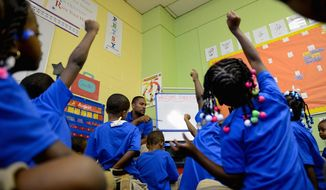 Kindergarten teacher Nick Brooks calls on eager students who raise their hands during a lesson in his classroom on the first day of school at DC Scholars Public Charter School in Southeast. (Photographs by Andrew Harnik/The Washington Times) **FILE**