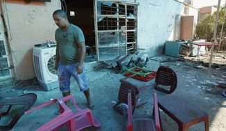 A man inspects the aftermath of a bomb attack at a coffee shop in the northeastern Shaab neighborhood of Baghdad, Iraq, Monday, Aug. 26, 2013. (AP Photo/Hadi Mizban)