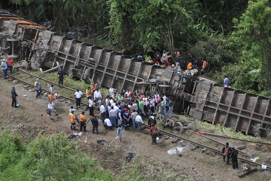 """Rescue workers try to evacuate the injured after a cargo train known as """"the Beast"""" derailed near Huimanguillo, Mexico, on Sunday, Aug. 25, 2013. The train, carrying at least 250 Central American hitchhiking migrants, derailed in a remote region, killing at least five people and injuring dozens, authorities said. (AP Photo/Tabasco State Government Press Office)"""