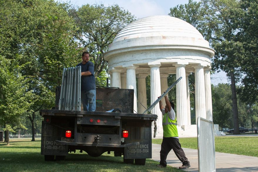 Event specialists unload fences to block off key locations and direct traffic in preparation for Wednesday's commemoration of the 1963 March on Washington. (Andrew S. Geraci/The Washington Times)