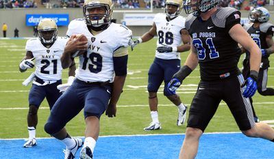 **FILE** Navy quarterback Keenan Reynolds, left, celebrates as he runs in for a touchdown past Air Force defensive back Brian Lindsay in the fourth quarter of Navy's 28-21 overtime victory in a college football game at Air Force Academy, Colo., on Saturday, Oct. 6, 2012. (AP Photo/David Zalubowski)