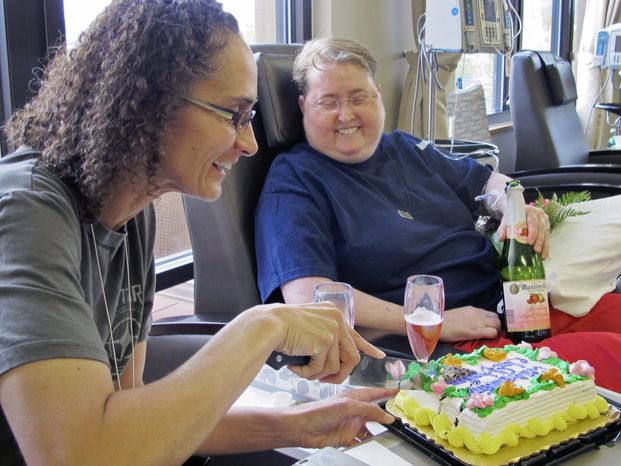 Angelique Neuman, left, and Jen Roper, right, celebrate their wedding at Christus St. Vincent Regional Cancer Center, where Roper is undergoing treatment, Friday Aug. 23, 2013 in Santa Fe, N.M. (AP Photo/The Albuquerque Journal, T.S. Last)