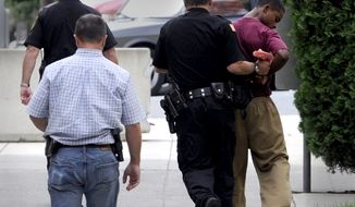 Demetrius Glenn (right), a teen who allegedly took part in the robbery and beating of 88-year-old World War II veteran Delbert Belton, is moved swiftly back to the juvenile detention center near the Spokane County Courthouse after a first appearance, via video, in District Court in Spokane, Wash., on Monday, Aug. 26, 2013. The youth, who will be charged as an adult, is charged with first-degree murder and first-degree robbery and was ordered held on $2 million bail. (AP/The Spokesman-Review, Jesse Tinsley)