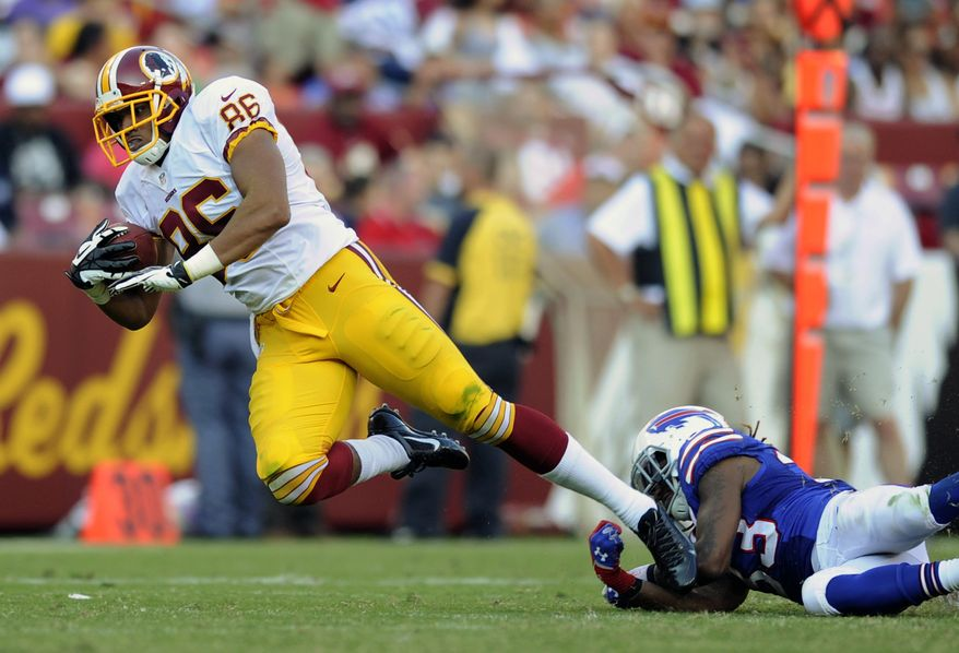 Washington Redskins tight end Jordan Reed, left, tries to slip past Buffalo Bills cornerback Ron Brooks in the second half of an NFL preseason football game Saturday, Aug. 24, 2013, in Landover, Md. (AP Photo/Nick Wass)