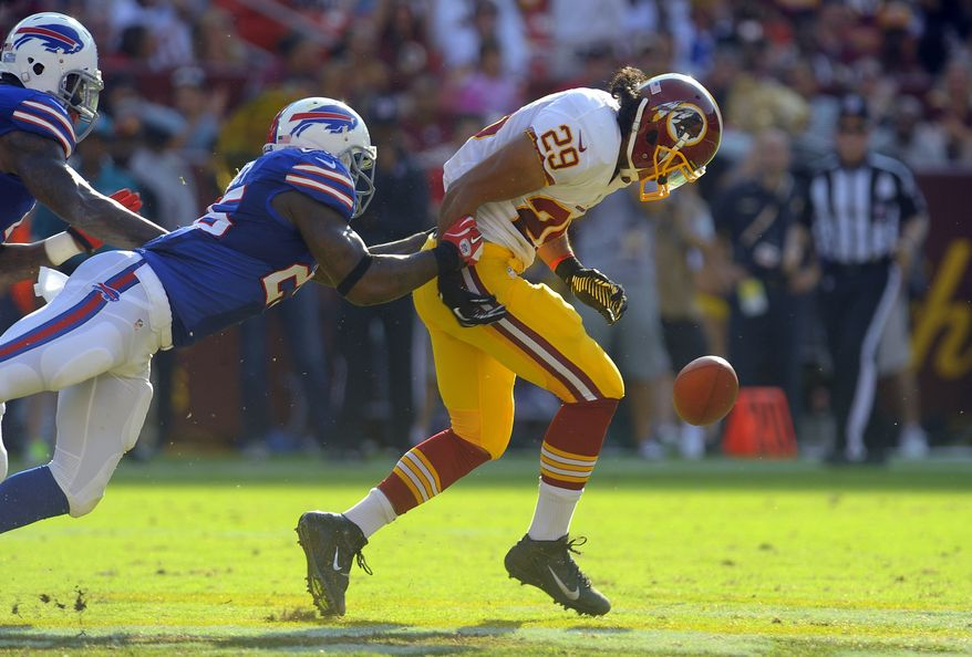 Washington Redskins running back Roy Helu (29) loses hold of the ball as he is tackled by Buffalo Bills strong safety Da'Norris Searcy in the first half of an NFL preseason football game Saturday, Aug. 24, 2013, in Landover, Md. Helu regained possession of the ball on the play. (AP Photo/Richard Lipski)