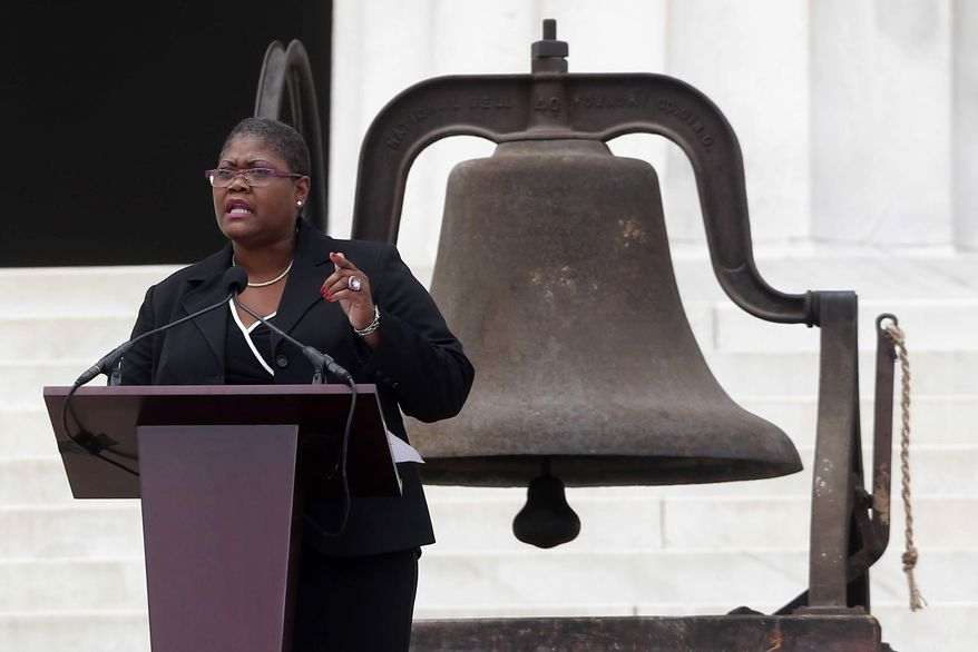 """Melanie Campbell, president and CEO of the National Coalition on Black Civic Participation, speaks at the Lincoln Memorial in Washington on Wednesday, Aug. 28, 2013, the 50th anniversary of the March on Washington, at which the Rev. Martin Luther King Jr. delivered his """"I Have a Dream"""" speech. The bell behind her rang at the 16th Street Baptist Church in Birmingham, Ala., the bombing of which 18 days after the 1963 march killed four young girls. (AP Photo/Charles Dharapak)"""