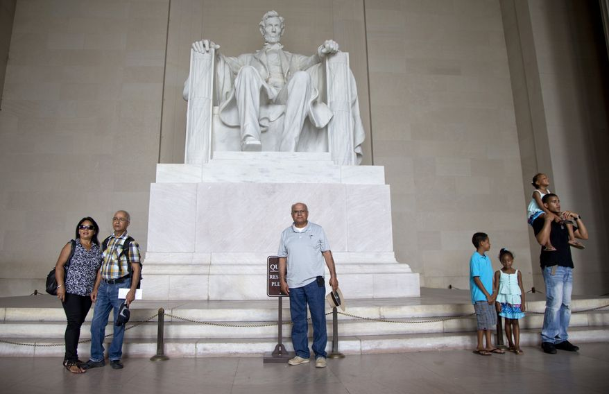 """Tourists stand in front  of the Lincoln Memorial in Washington, Tuesday, Aug. 27, 2013, as they are photographed. Preparations for the 50th anniversary of the March On Washington celebrations that will be held Wednesday, Aug, 28, 2013 are underway.  Barack Obama was 2 years old and growing up in Hawaii when Martin Luther King Jr. delivered his """"I Have a Dream"""" speech from the steps of the Lincoln Memorial. Fifty years later, the nation's first black president will stand as the most high-profile example of the racial progress King espoused, delivering remarks at a nationwide commemoration of the 1963 demonstration for jobs, economic justice and racial equality.   (AP Photo/Carolyn Kaster)"""